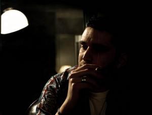 Мужчина курит сигарету под резким светом